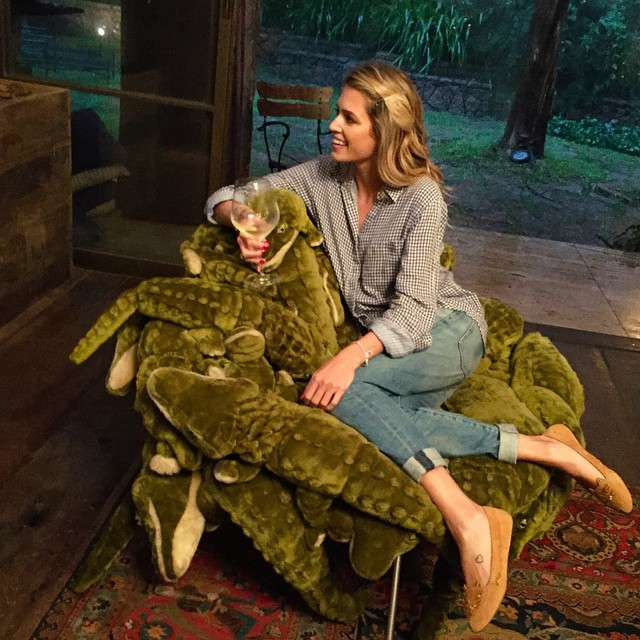 helena bordon chilling with a glass of wine on a crocodile chair